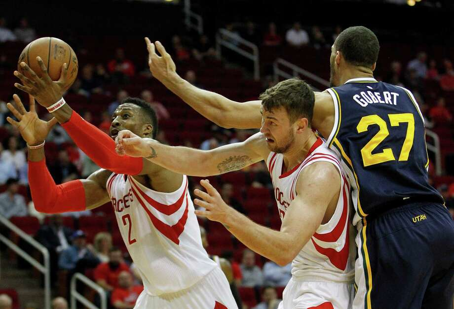 Houston Rockets forward Donatas Motiejunas (20) gets caught in the middle of a scramble for a loose ball against Rockets center Dwight Howard (12) and Utah Jazz center Rudy Gobert (27) during the first half of an NBA basketball game at Toyota Center, Wednesday, March 23, 2016. Photo: Karen Warren, Houston Chronicle / © 2016  Houston Chronicle