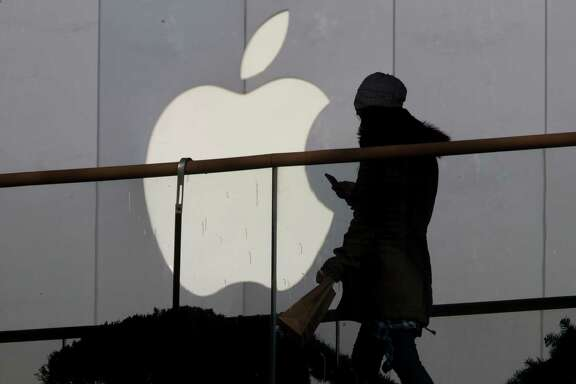 A woman uses an Apple iPhone in Beijing. This week, the Justice Department said a third party had offered a potential solution for breaking into a suspected terrorist's iPhone without wiping the data from the device.