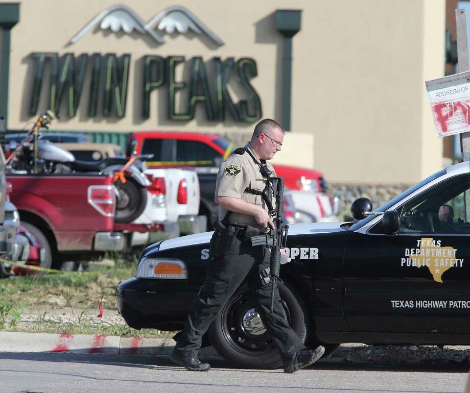 Authorities investigate the scene following a wild shootout between rival biker gangs at the Twin Peaks restaurant in Waco last May. Photo: Jerry Larson / AP / FR91203 AP