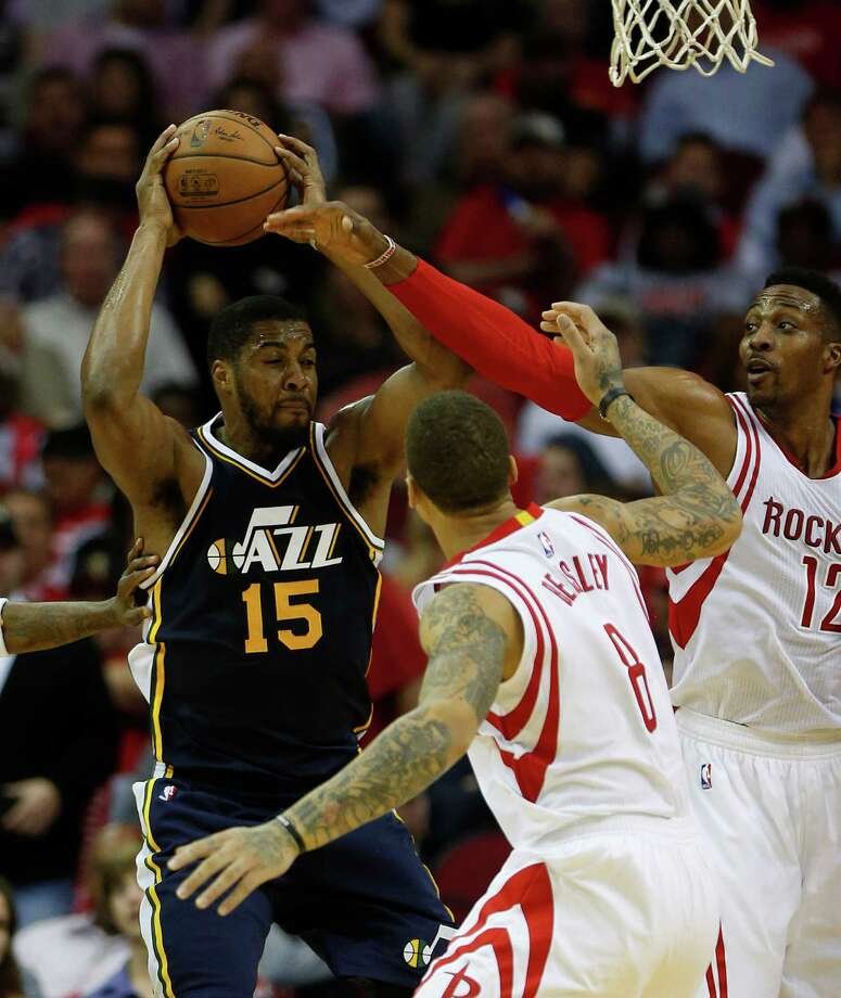 Utah Jazz forward Derrick Favors (15) looks to pass the ball against Houston Rockets center Dwight Howard (12) and  forward Michael Beasley (8) during the second half of an NBA basketball game at Toyota Center, Wednesday, March 23, 2016.  ( Karen Warren / Houston Chronicle ) Photo: Karen Warren, Staff / © 2016  Houston Chronicle