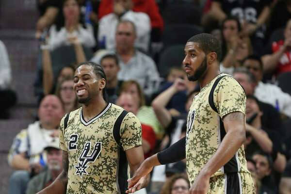 While grimacing, San Antonio Spurs' Kawhi Leonard gets a five from LaMarcus Aldridge during the second half at the AT&T Center, Wednesday, March 23, 2016. The Spurs won, 112-88. Leonard suffered a slight injury in the play and left after shooting a foul shot.