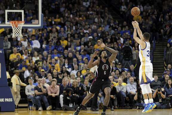 Stephen Curry (30) shoots a three pointer over Deandre Jordan (6) in the second half as the Golden State Warriors played the Los Angeles Clippers at Oracle Arena in Oakland, Calif., on Wednesday, March 23, 2016.