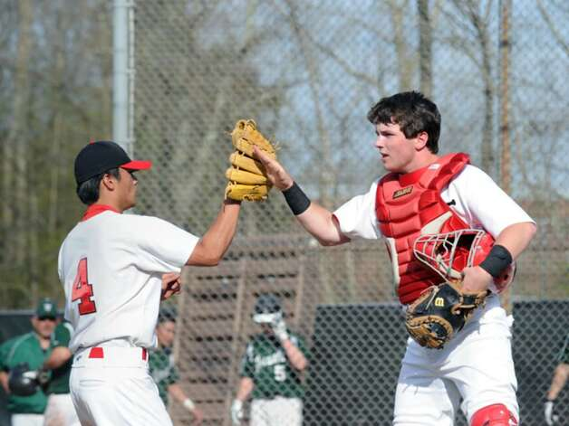 GHS pitcher, Yuta Okazaki, left and GHS catcher, Ryan Brennan, right, high five after Okazaki was able to pitch out of a jam in the early innings of a 4-1 victory over Norwalk High School during the GHS home opner, April 7, 2010. Photo: Bob Luckey / Greenwich Time