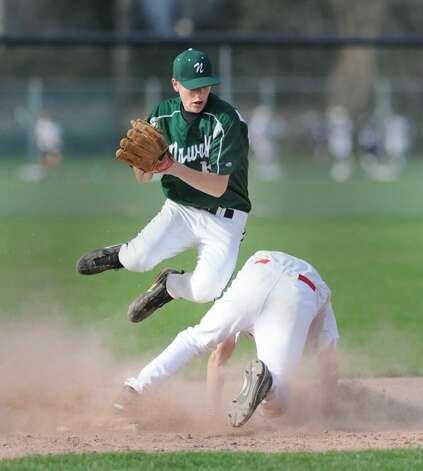 Second baseman, Sean Whitteaker, # 16 of Norwalk High School, goes in the air as he gets the force out at 2nd base as Casey Gaynor, # 10 of Greenwich High School, disrupts the throw attempt leaving the runner safe at lst base during a Greenwich High School 4-1 victory over Norwalk High School, Wednesday, April 7, 2010. Photo: Bob Luckey / Greenwich Time