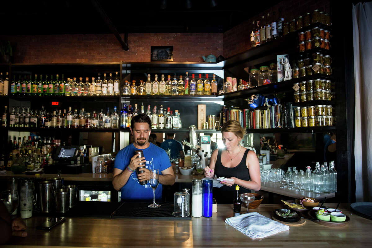Jesse Torres and Amber Gibson work behind the bar at Mezcalaria Mixtli. The bar announced over the weekend that it's closing.
