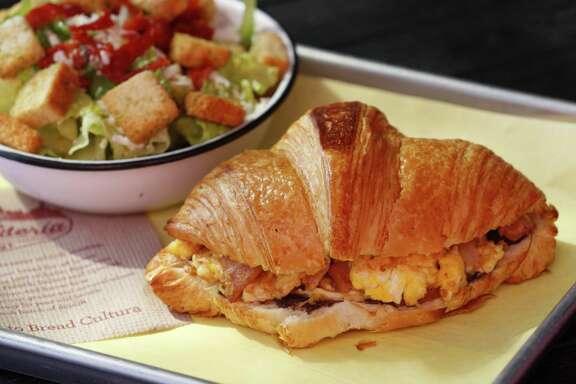 The ham and egg sandwich from La Panadería is served with a dab of black beans on a buttery, flaky croissant.