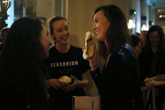 Emma Powers (right) jokes around with a pointe shoe as dancers Samantha Bristow (left) and Maggie Weirich laugh during Sensorium at the War Memorial Opera House in San Francisco, California, on Wednesday, March 23, 2016.