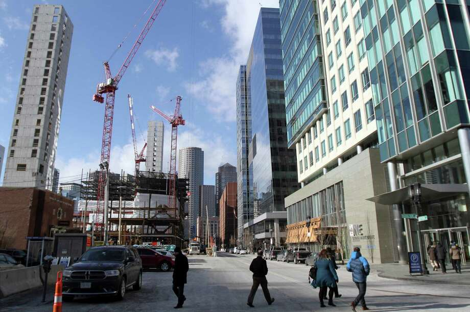 Construction takes place on two buildings, left, adjacent to three recently built buildings, right, in the Seaport District, Thursday, Jan. 14, 2016, in Boston. General Electric said Wednesday it will begin relocating its global headquarters to the district in the summer from Fairfield, Conn., and complete the move by 2018. Boston's Seaport District long was filled with docks, warehouses and parking lots. But in recent years it has become the city's hottest and fastest-growing neighborhood. Photo: Bill Sikes / Associated Press / Associated Press