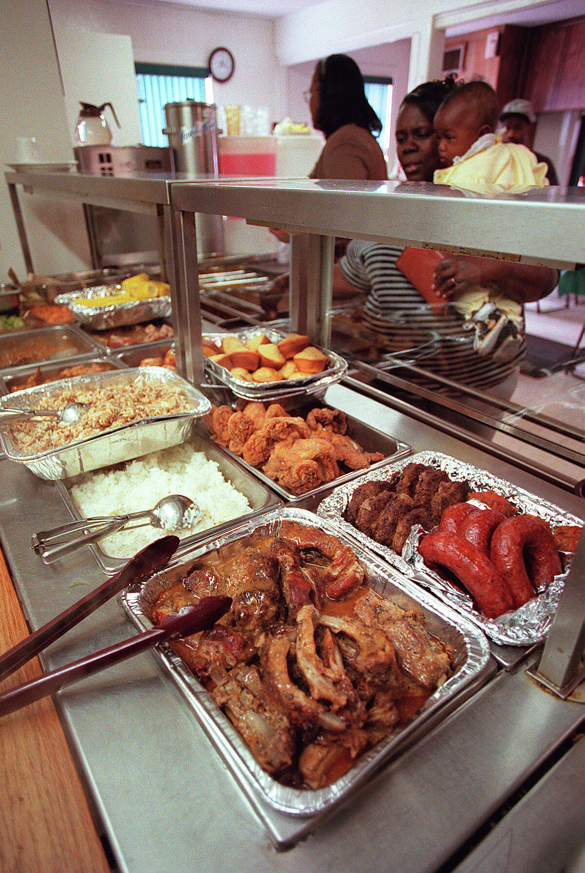 The buffet line includes fried chicken , saudage, pork ribs, cornbread, sweet potatoes, greens, squash and corn on the cob.