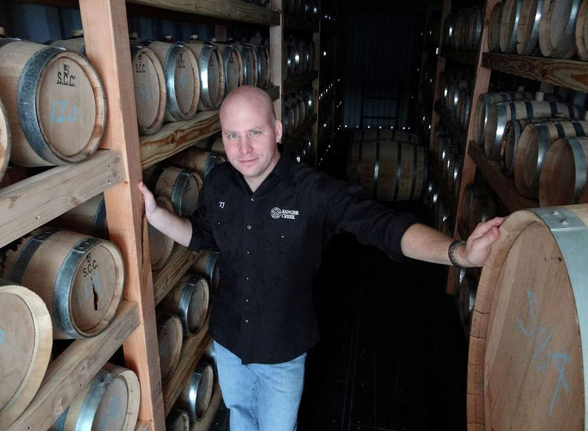 T.J. Miller of Ranger Creek Brewing and Distilling stands amid barrels of aging bourbon in the facility's rackhouse on Saturday, Oct. 8, 2011. BILLY CALZADA / gcalzada@express-news.net