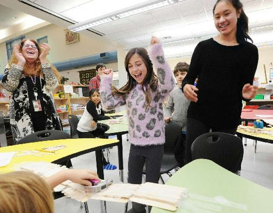 Cos Cob School fourth-graders work with Greenwich High School junior Margaret Cirino on suspension bridge building during a January meeting of the school's STEM Explorers Club in the innovation space in the school's media center. Photo: Bob Luckey
