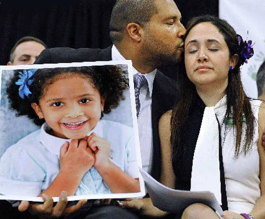 Jimmy Greene kisses his wife Nelba Marquez-Greene as he holds a portrait of their daughter, Sandy Hook School shooting victim Ana Marquez-Greene, at a news conference in Newtown. Photo: Jessica Hill / AP