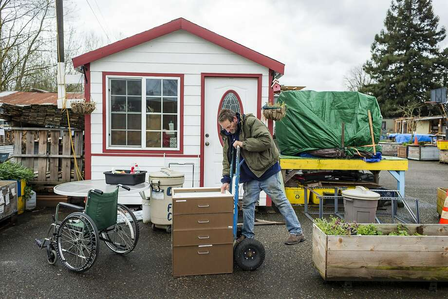 Dignity Village resident Ken Irish loads up a shelf unit he found to use in his home. Photo: Christopher Onstott, Special To The Chronicle