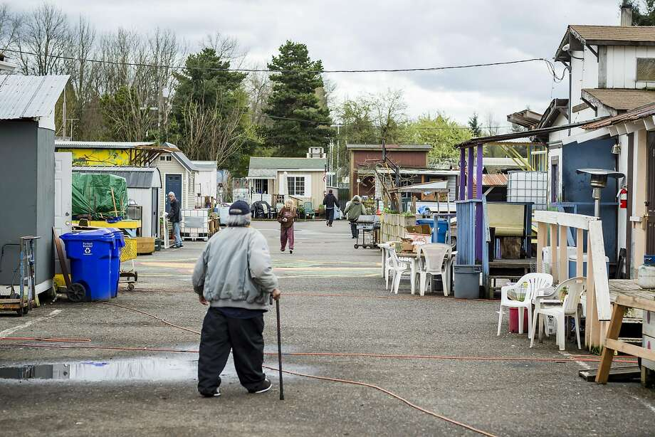 """Residents of the Dignity Village tiny house community walk up and down """"Main Street."""" Photo: Christopher Onstott, Special To The Chronicle"""