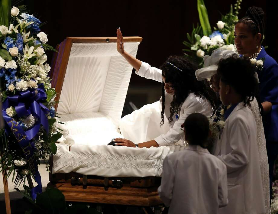 Audrey Hughes Cornish raises one hand and places the other on son Torian Hughes during the 17-year-old's funeral at Shiloh Church in Oakland in January. Photo: Connor Radnovich, The Chronicle
