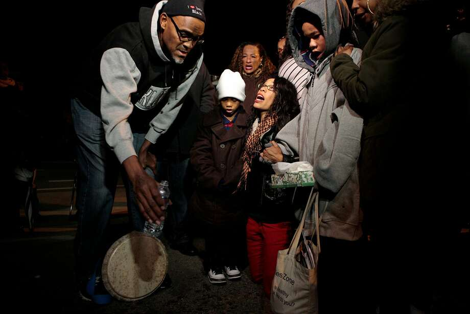 Audrey Hughes Cornish (center) mourns her slain son, Torian Hughes, during a ceremony where water is poured on the concrete in his memory at 10th Street and Mandela Parkway in Oakland. Photo: Nathaniel Y. Downes, Special To The Chronicle