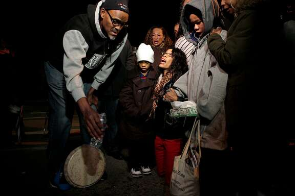 Audrey Hughes Cornish (center) greaves her son, Torian Hughes,  during a ceremony where water is poured on the cement in his honor at 10th Street & Mandela Parkway on Thursday, Dec. 24, 2015 in Oakland, Calif.