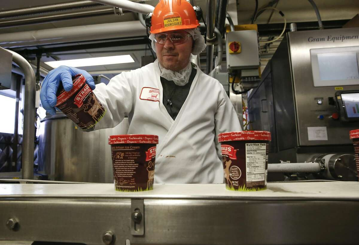 Julian Rodriguez, works the line where pints of organic non-GMO dutch chocolate ice cream are being produced at the processing plant of the organic dairy Straus Family Creamery in Marshall, California, on Thurs. March 24, 2016.