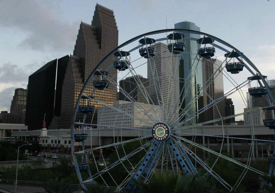 Ferris wheel riders at the Downtown Aquarium enjoy the many colors of the buildings in downtown as the sun sets in Houston. Photo: Carlos Antonio Rios, Staff Photographer / Houston Chronicle