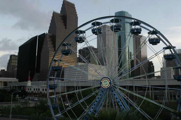 Ferris wheel riders at the Downtown Aquarium enjoy the many colors of the buildings in downtown as the sun sets in Houston.