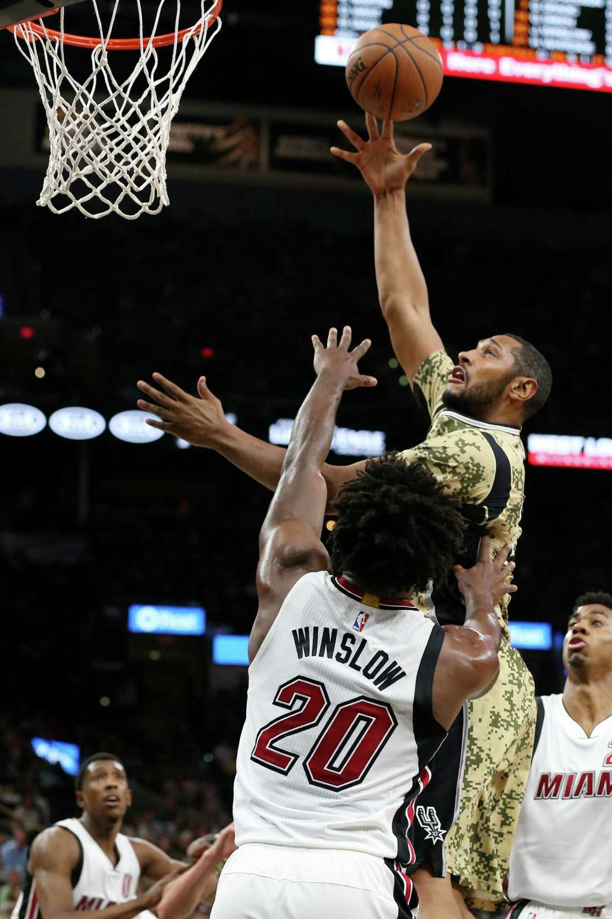 San Antonio Spurs' Boris Diaw shoots over Miami Heat's Justise Winslow during the first half at the AT&T Center, Wednesday, March 23, 2016.