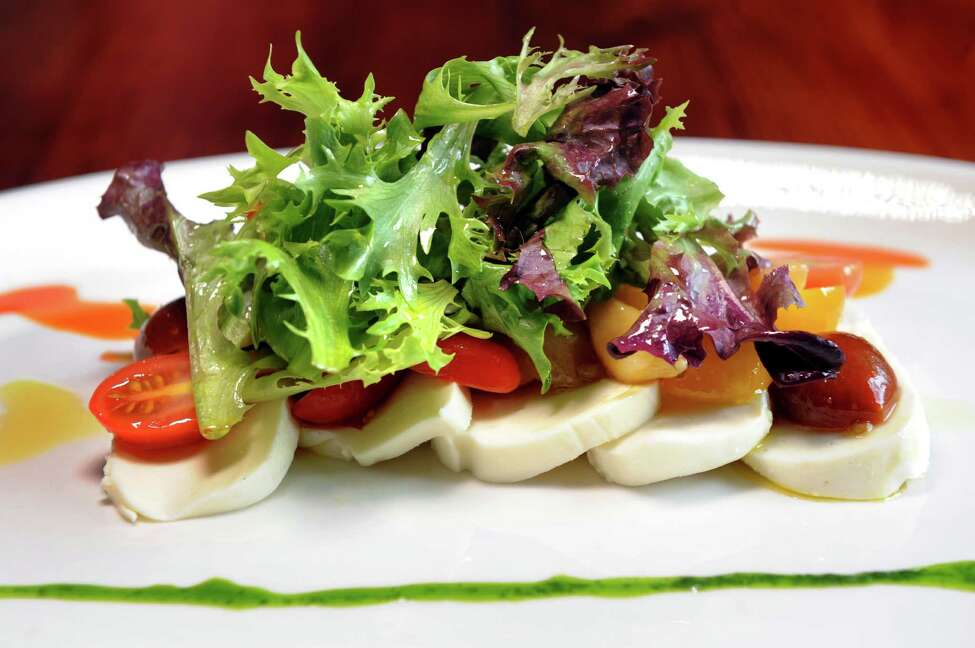 Salade de Tomates et Fromage has fresh mozzarella, marinated heirloom tomatoes, roasted garlic cloves, baby greens, parsley oil, lemon oil and Piment d'Esplette oil on Friday, March 18, 2016, at Chez Nous in Schenectady, N.Y. (Cindy Schultz / Times Union)