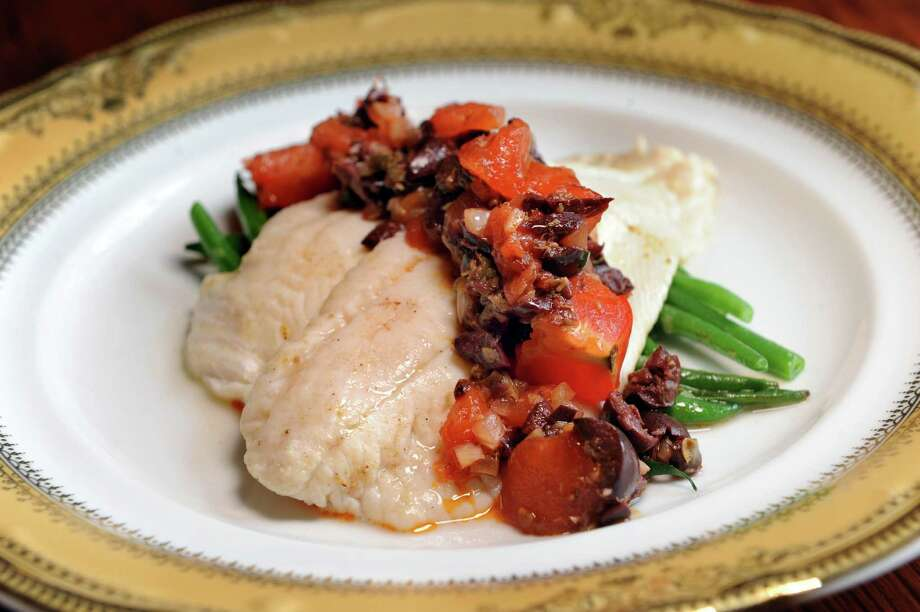 Poisson du Jour Poele a la Provencale is a 10-ounce butter pan-fried filet, topped with Provencale-style sauce of garden tomatoes, kalamata olives, capers, onions, garlic and lemon zest served with vegetable du jour on Friday, March 18, 2016, at Chez Nous in Schenectady, N.Y. (Cindy Schultz / Times Union) Photo: Cindy Schultz / Albany Times Union