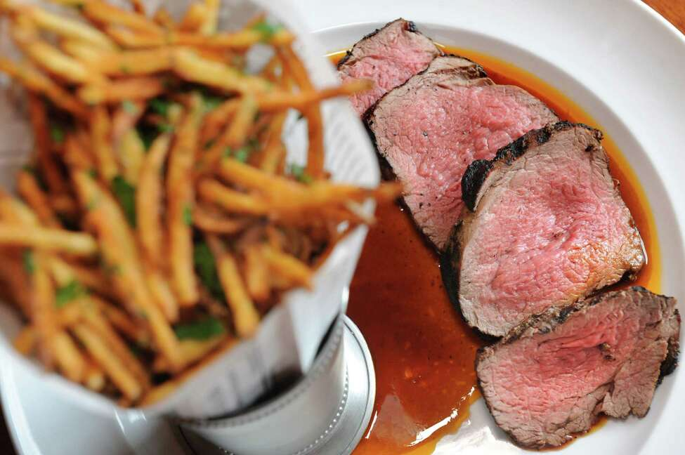 Les Grillades de Chateaubriand is sliced, chargrilled, marinated 10-ounce tenderloin of beef served with truffled deep-fried matchstick potatoes and Sauce Chez Nous on Friday, March 18, 2016, at Chez Nous in Schenectady, N.Y. (Cindy Schultz / Times Union)