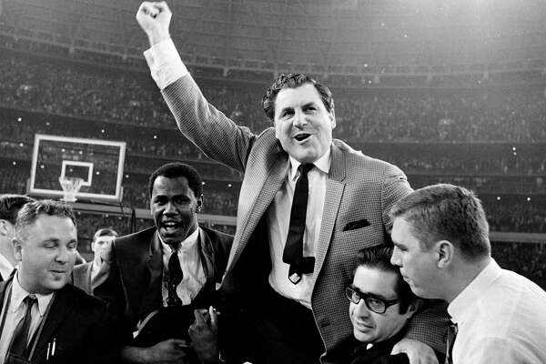 Guy V. Lewis, University of Houston basketball coach, lets out a war whoop as he is carried to the dressing room by happy fans after the Houston Cougars' upset over the UCLA Bruins in the Houston Astrodome, Jan. 20, 1968. (AP Photo/Ed Kolenovsky)