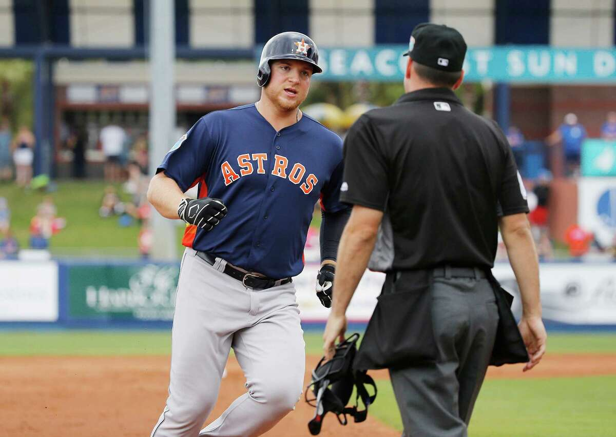 Houston Astros' A.J. Reed rounds third base while looking to the umpire after New York Mets' left fielder Yoenis Cespedes pleads for a ground rule double during the second inning of an exhibition spring training baseball game, Thursday, March 24, 2016, in Port St. Lucie, Fla. Reed was credited with an inside-the-park home run (AP Photo/Brynn Anderson)