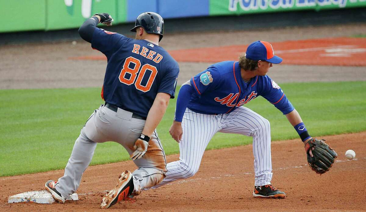 Houston Astros' A.J. Reed safely tags third base against New York Mets' Jeff McNeil during the seventh inning of a spring training baseball game, Thursday, March 24, 2016, in Port St. Lucie, Fla. (AP Photo/Brynn Anderson)