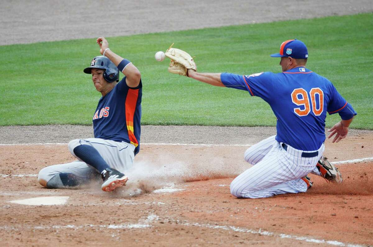 Houston Astros' Carlos Correa, safely slides into home plate after a wild pitch by New York Mets' Beck Wheeler, during the fourth inning of an exhibition spring training baseball game, Thursday, March 24, 2016, in Port St. Lucie, Fla. (AP Photo/Brynn Anderson)