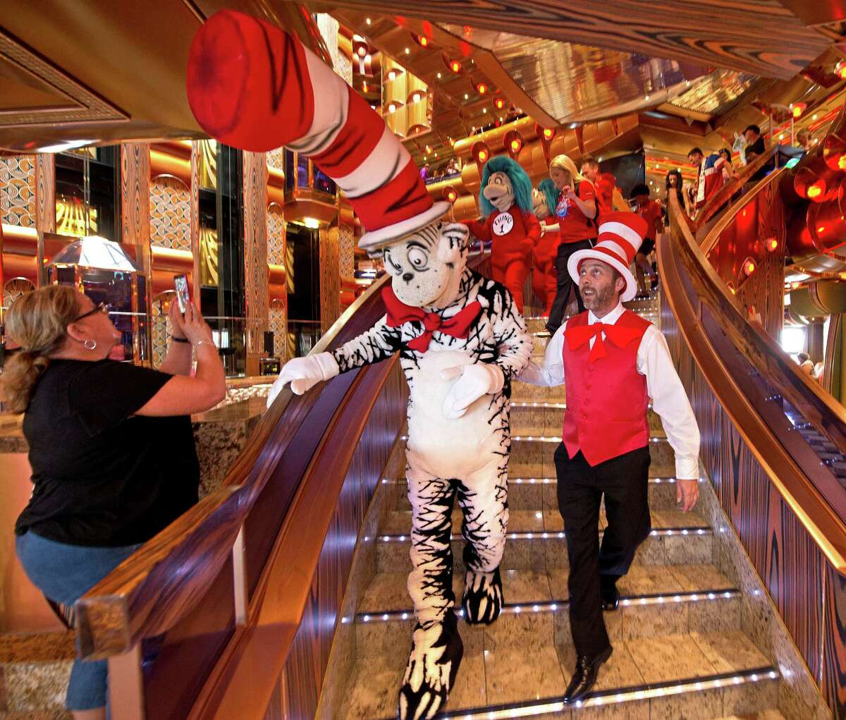 The Cat-in-the-Hat and other Dr. Seuss characters descend the Millennium Atrium's staircase during the Seuss-a-palooza parade on the Carnival Freedom. The procession is one of several facets of a Carnival Seuss at Sea program that offers a variety of exciting and immersive onboard youth, family, dining and entertainment experiences featuring the amazing world and words of Dr. Seuss.