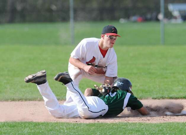 GHS shortstop, Michael Dunster, # 24, puts the tag on Chris Kassimis, # 9, of NHS during an unsuccessful pick-off during Greenwich High School vs. Norwalk High School game in which Greenwich High School won 4-1, April 7, 2010. Photo: Bob Luckey / Greenwich Time