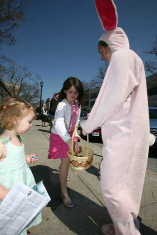 Anastasia Freccia got into the spirit of Easter and handed out candy along Greenwich Avenue Sunday morning. Photo: David Ames, David Ames/For Greenwich Time / Greenwich Time