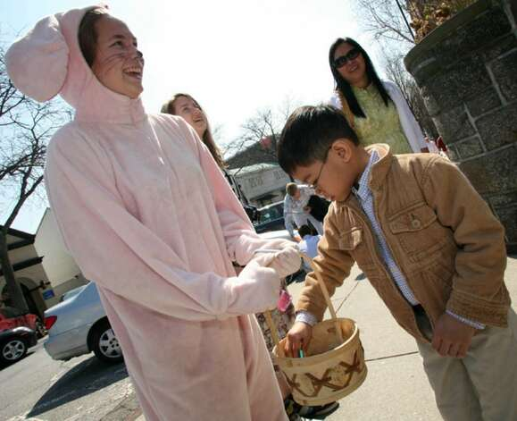 Owen Ante gets some candy from the Easter Bunny, aka. Anastasia Freccia, as she made her way down Greenwich Avenue Sunday morning. Photo: David Ames, David Ames/For Greenwich Time / Greenwich Time
