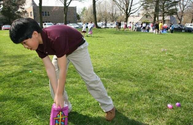 Second Congregational Church member Conor Li searches for eggs during an easter egg hunt held at the church Easter morning. Photo: David Ames, David Ames/For Greenwich Time / Greenwich Time