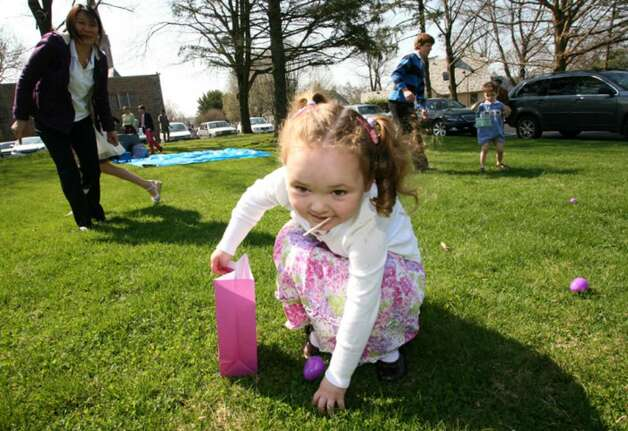 Samantha Packer collects eggs during an easter egg hunt held at the Second Congregational Church Sunday morning. Photo: David Ames, David Ames/For Greenwich Time / Greenwich Time