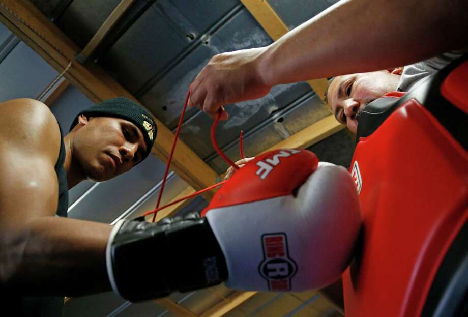 San Antonio's Alex Rios Jr. has his gloves laced up by his father, Alex Sr., on March 23, 2016 Photo: Ronald Cortes /For The Express-News