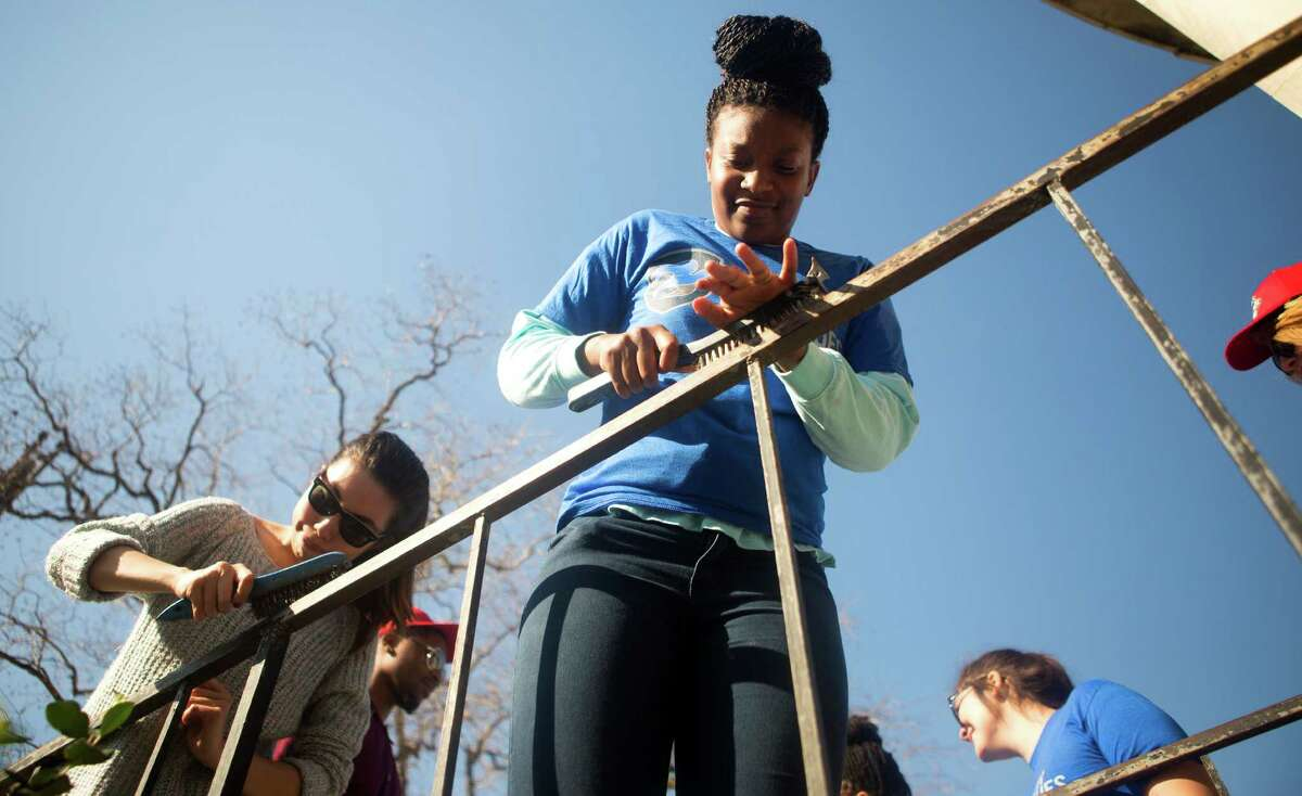 Deneesha Jones, right, uses a wire brush on a rail as she, and other volunteers work on the Blue Triangle Community Center during Martin Luther King Jr. Day of Service in Houston. The 2016 NCAA Men's Final Four Local Organizing Committee collaborated with Mission Continues, to organize 300 volunteers as they cleaned, organized and beautified the community center in the Third Ward.. (Cody Duty / Houston Chronicle)