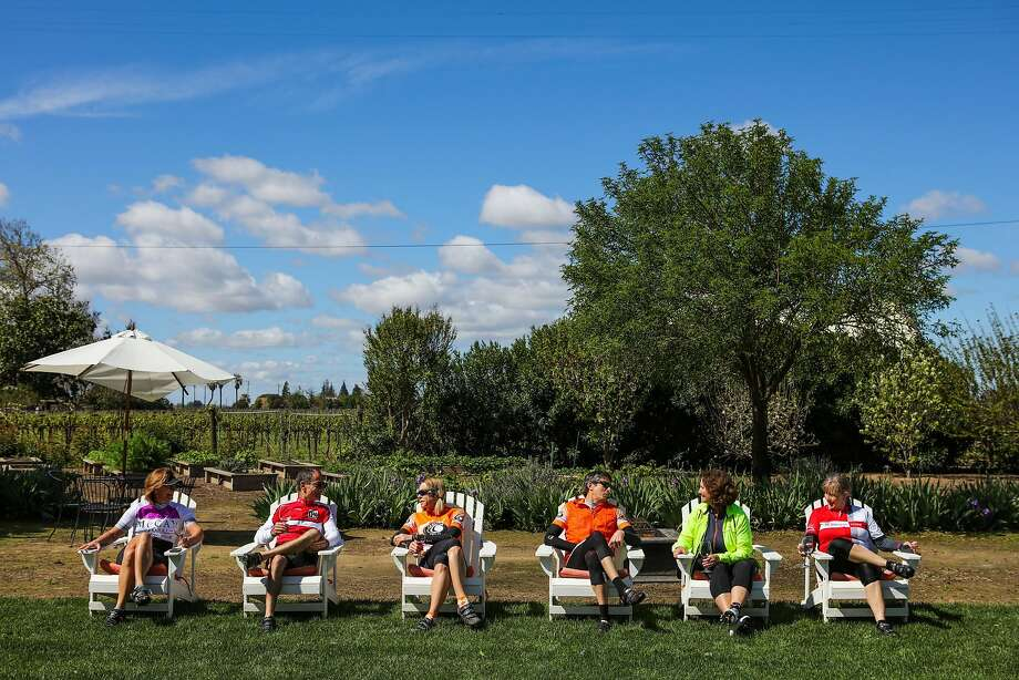 "Dianna Stein, Bill Mitchell, Anita Herman, Andy Grutman, Kandy Vaccarezza, and Lynn Fields chat as they sip wine at Durst Winery, in Lodi, California, on Tuesday, March 22, 2016. The cycling group, which started out as the ""Bike Chicks"" bike over thirty miles a few times a week through Lodi. Photo: Gabrielle Lurie, Special To The Chronicle"