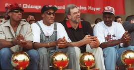 Chicago Bulls, from left: Dennis Rodman, Scottie Pippen, coach Phil Jackson, and Michael Jordan, sit with four NBA trophies at their feet during the championship celebration Tuesday, June 18, 1996, in Chicago's Grant Park. The Bulls have won four NBA titles in six years; and, the hometown heroes promised the thousands of fans gathered Tuesday, more championships to come. (AP Photo/ Beth A. Keiser)