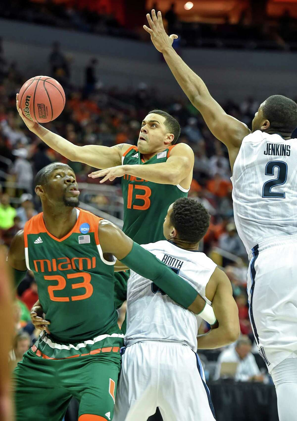 Miami's Angel Rodriguez (13) drives to the basket against Villanova's Phil Booth (5) in the first half during a Sweet 16 matchup in the NCAA Tournament's South region at the KFC Yum! Center in Louisville, Ky., on Thursday, March 24, 2016.