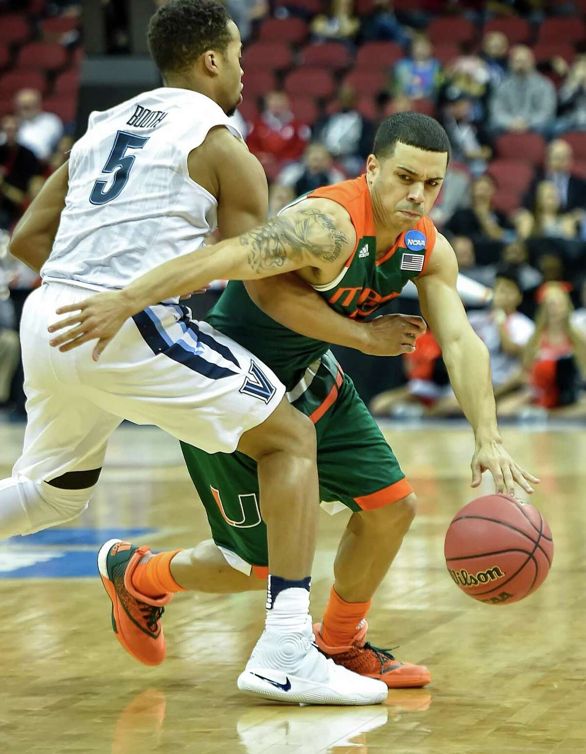 Miami's Angel Rodriguez (13) drives against Villanova's Phil Booth (5) in the first half during a Sweet 16 matchup in the NCAA Tournament's South region at the KFC Yum! Center in Louisville, Ky., on Thursday, March 24, 2016.