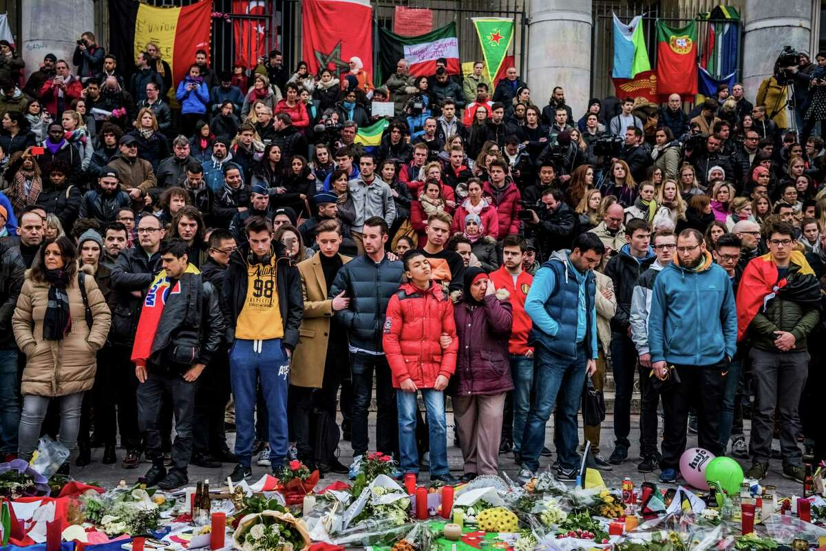 Surrounded by international flags, people pay tribute to victims of multiple attacks across Brussels, during a moment of silence at Place de la Bourse, in Brussels, March 24, 2016. Tuesday's deadly suicide bombings at the city?'s main airport and at a subway station in central Brussels killed at least 31 people and injured 270. (Daniel Berehulak/The New York Times)