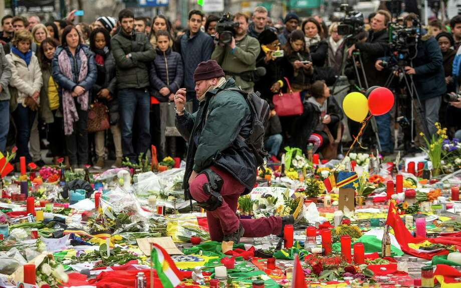 A man kneels and makes the sign of the cross Thursday during a minute of silence held at a makeshift memorial in front of Brussel's Stock Exchange on Place de la Bourse,  two days after a triple bomb attack, claimed by the Islamic State group, hit the airport and a busy metro station, killing 31 and wounding 300. Photo: PHILIPPE HUGUEN, Staff / AFP or licensors