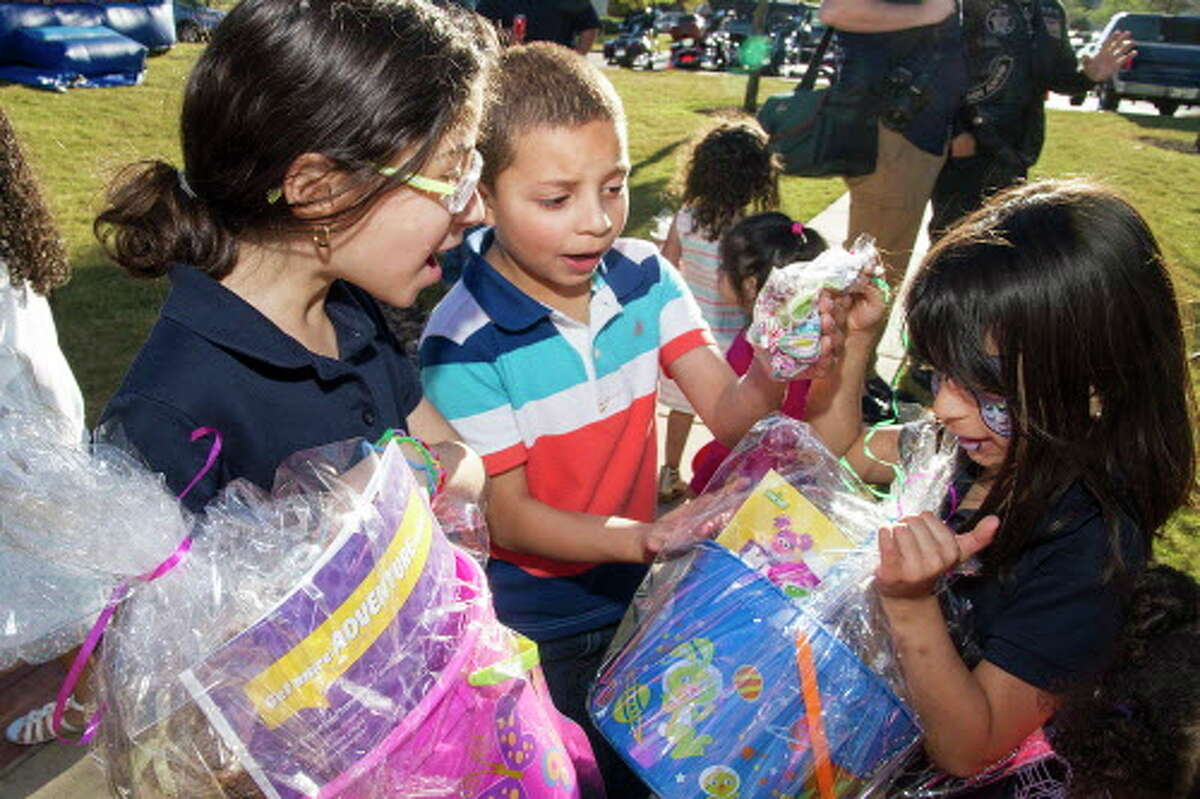 (Left to right) Paola Areizaga, 10, Jadiel Perez, 8, and Janelle Areizaga, 6, react to finding candy in their egg baskets, Thursday, March 24, 2016, at San Antonio Village. Operation Homefront Village and the Brothers in Christ Motorcycle Ministry celebrated an