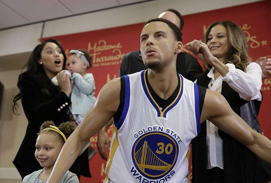 Ayesha Curry, left, reacts as Sonya Curry, right, takes a closer look at a wax figure of her son, Golden State Warriors guard Stephen Curry, after its unveiling Thursday, March 24, 2016, in Oakland, Calif. The figure of the NBA MVP will go on display at Madame Tussauds wax museum at Fisherman's Wharf in San Francisco. Ayesha Curry, wife of Stephen Curry, holds their daughter Ryay, as their other daughter, Riley, stands below. (AP Photo/Eric Risberg) Photo: Eric Risberg, AP
