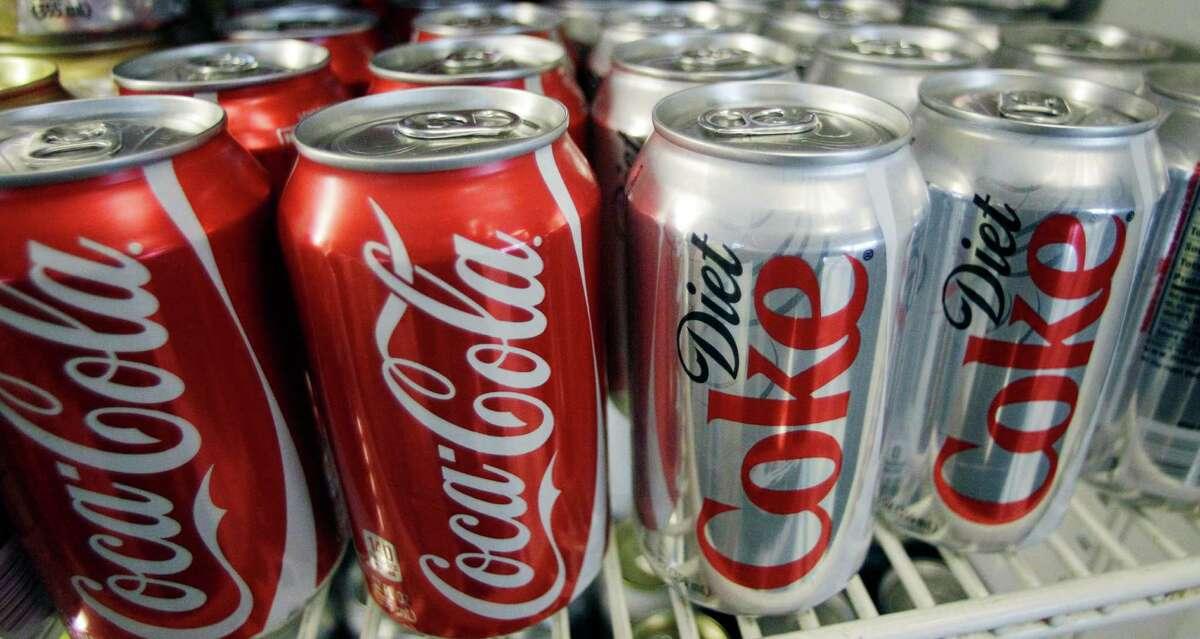 FILE - In this March 17, 2011, file photo, cans of Coca-Cola and Diet Coke sit in a cooler in Anne's Deli in Portland, Ore. Coca-Cola announced in Paris on Tuesday, Jan. 19, 2016, that a campaign, called