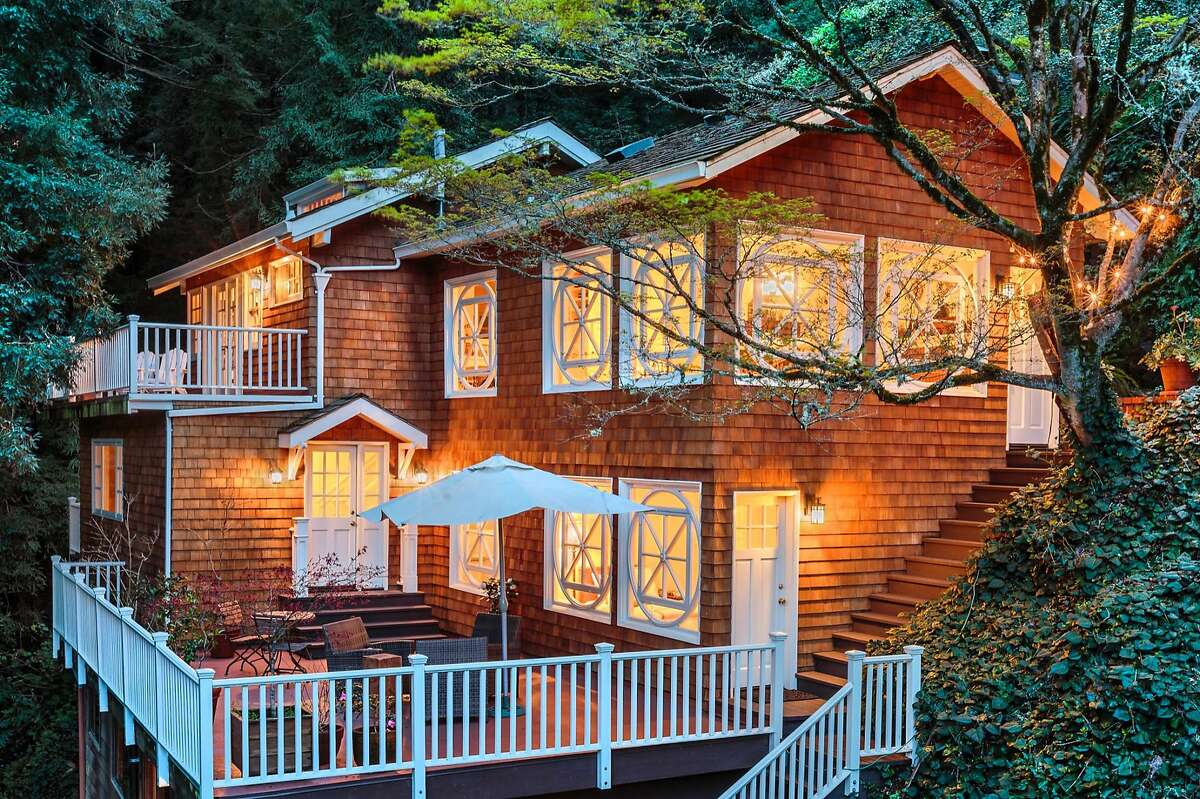 This twilight picture showcases decks off the lower level's master suite and the top floor living room.�
